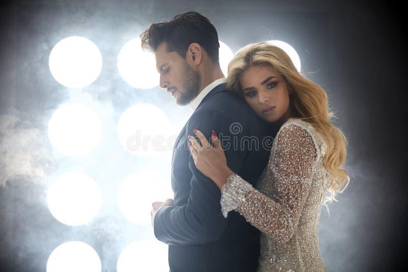 拥抱一个英俊的人的可爱的白肤金发的夫人 图库摄影