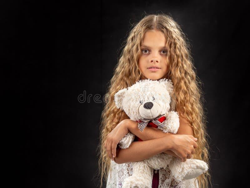 拥抱一头老软的玩具熊一个十几岁的女孩的画象 库存照片