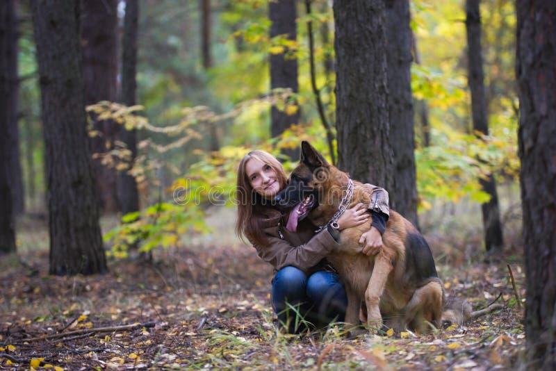 拥抱一条德国牧羊犬狗的年轻逗人喜爱的妇女户外在秋天森林里 库存图片