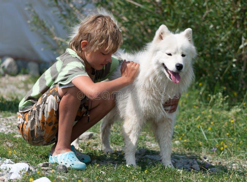 拥抱一条蓬松狗的男孩 库存照片