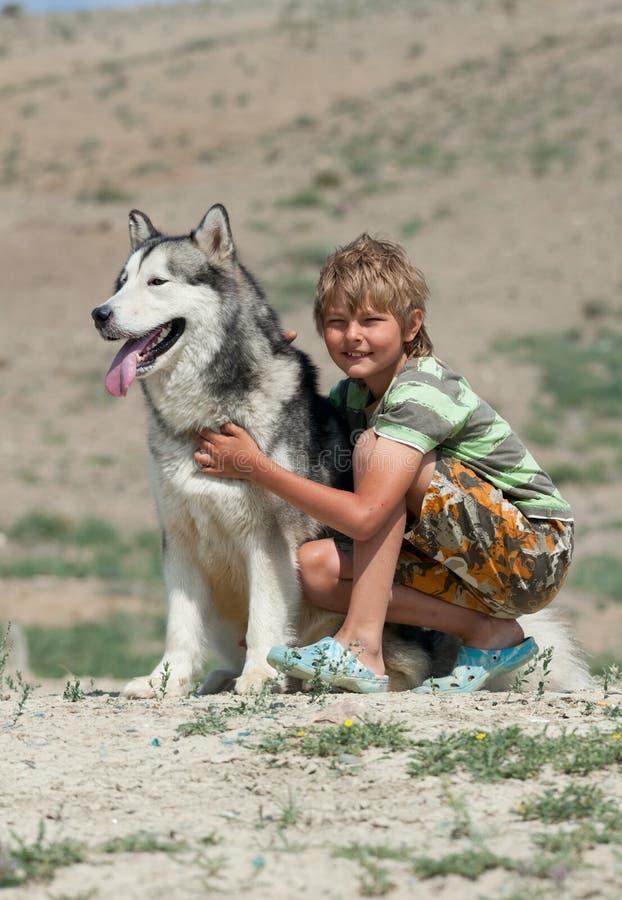拥抱一条蓬松狗的男孩 免版税库存照片