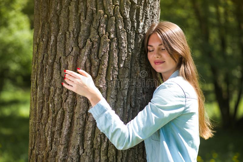 拥抱一棵大树的妇女 免版税库存图片