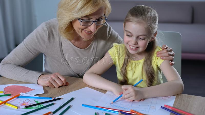 拥抱一点孙女,俏丽的女孩绘画房子,家庭的年长祖母 免版税图库摄影