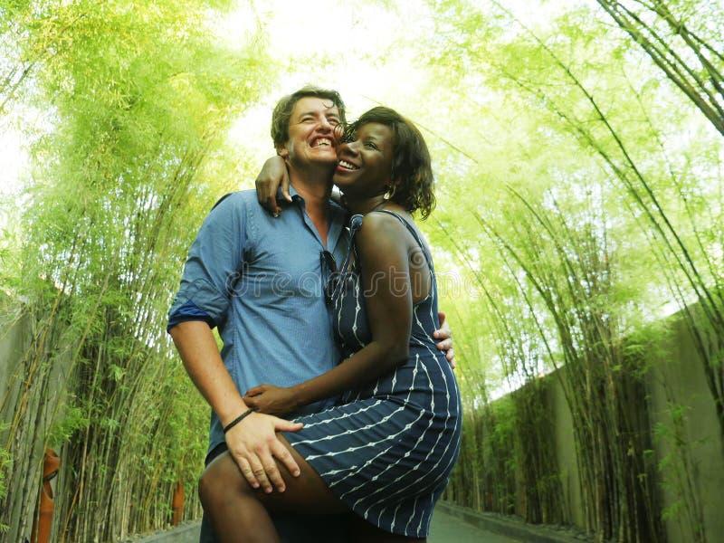 拥抱与可爱的黑人美国黑人的女朋友的有吸引力和愉快的混杂的种族夫妇或妻子和英俊的白种人 库存图片