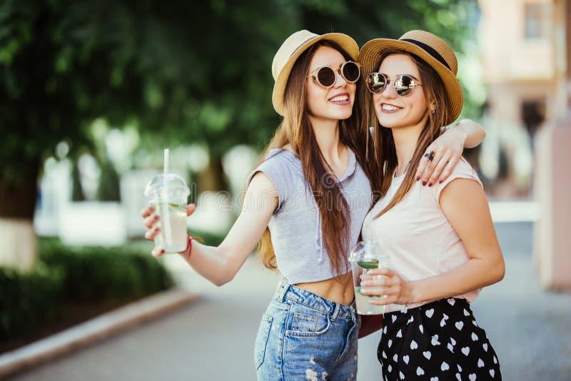 拥抱与在街道上的鸡尾酒的两个时髦的女孩的愉快的正面片刻在城市 特写镜头画象滑稽快乐attarctive您 免版税库存照片