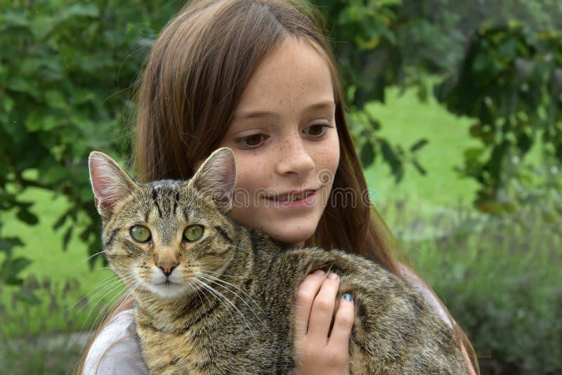 拥抱与她的猫的女孩 免版税库存照片