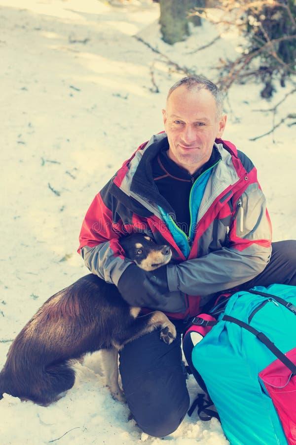 拥抱与狗的微笑的远足者 免版税图库摄影