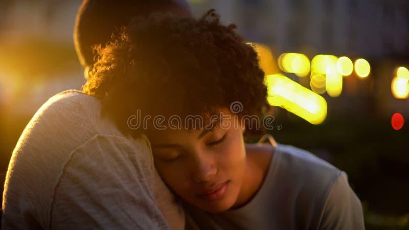 拥抱与男朋友的逗人喜爱的美国黑人的妇女,一起信任关系 库存图片