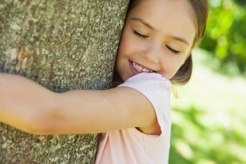 拥抱与眼睛的微笑的女孩树在公园关闭了 库存照片