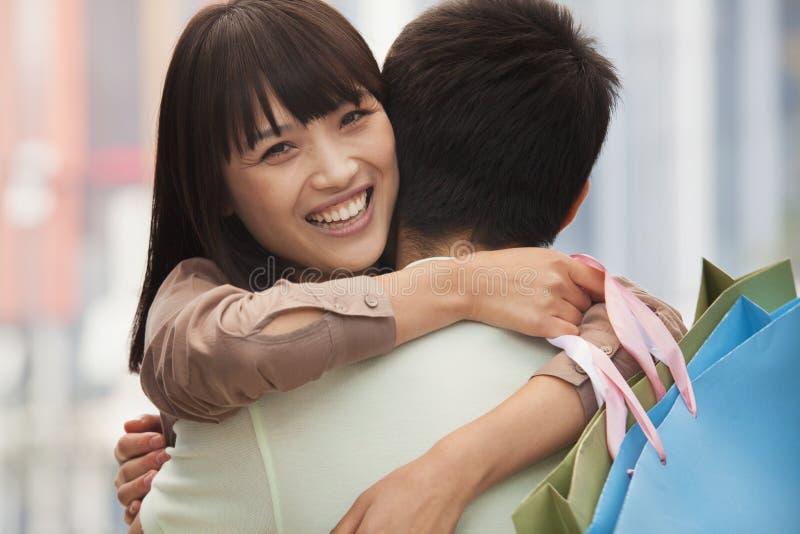 拥抱与购物袋的年轻夫妇,户外,北京 库存图片