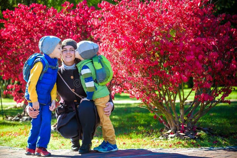 拥抱两个小孩,幸福家庭,有两室外的儿子的逗人喜爱的深色的女性特写镜头画象的年轻母亲的图片  库存照片