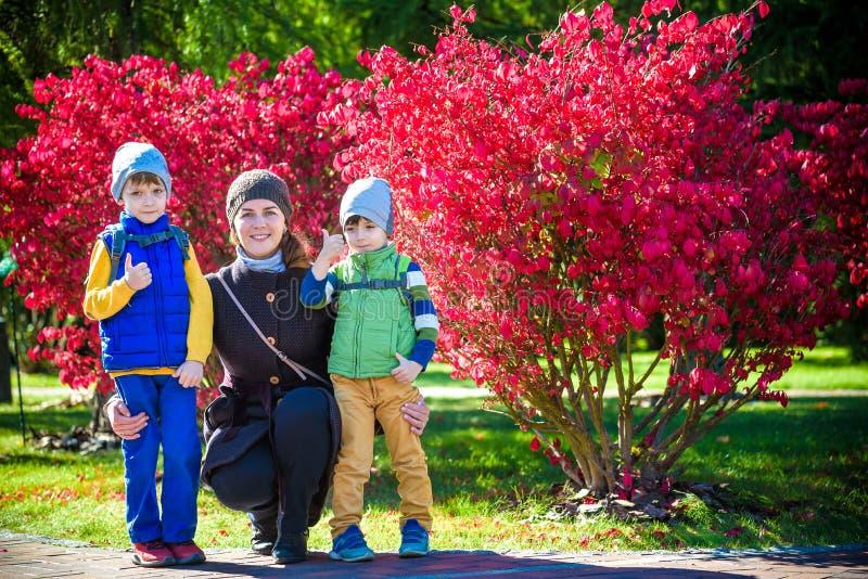 拥抱两个小孩,幸福家庭,有两室外的儿子的逗人喜爱的深色的女性特写镜头画象的年轻母亲的图片  免版税库存图片