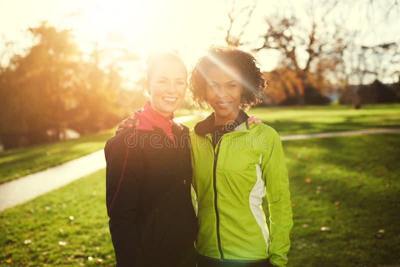 拥抱两个年轻的女运动员,当站立在公园时 库存照片