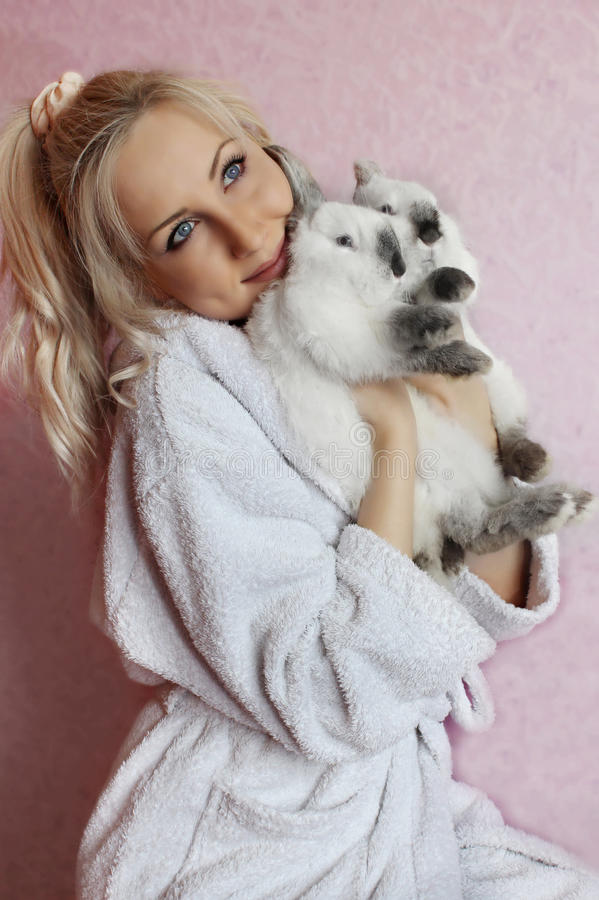 拥抱两只兔子的女孩 库存照片