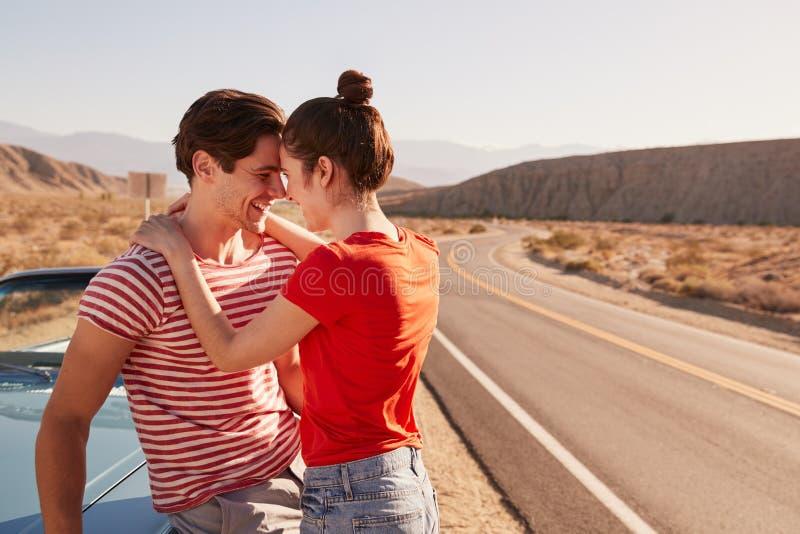 拥抱乘他们的汽车的年轻白色夫妇在路旁 库存图片