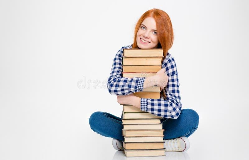 拥抱书和微笑的可爱的逗人喜爱的相当少妇 免版税库存照片