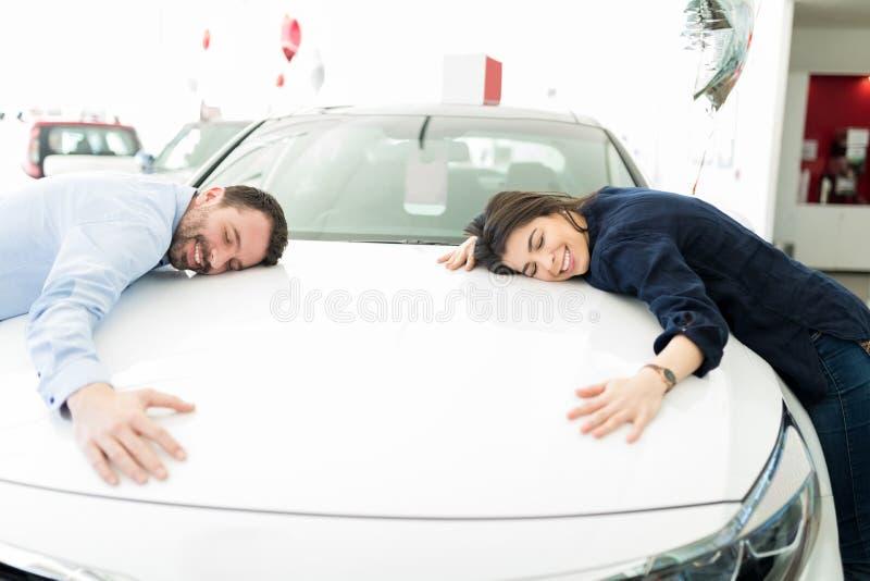 拥抱他们的第一辆汽车的微笑的男人和妇女 库存图片