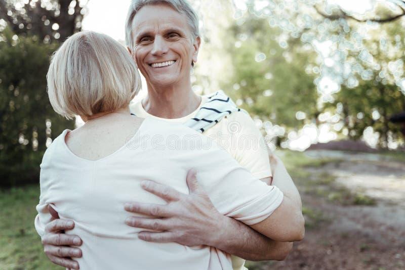 拥抱他的妇女的愉快的成熟人 免版税图库摄影
