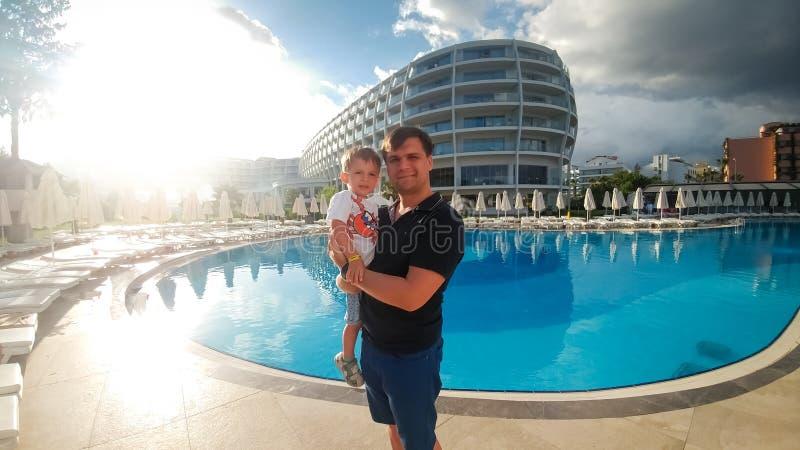 拥抱他的小孩儿子的愉快的年轻父亲画象反对大游泳场在旅馆手段 r 库存图片