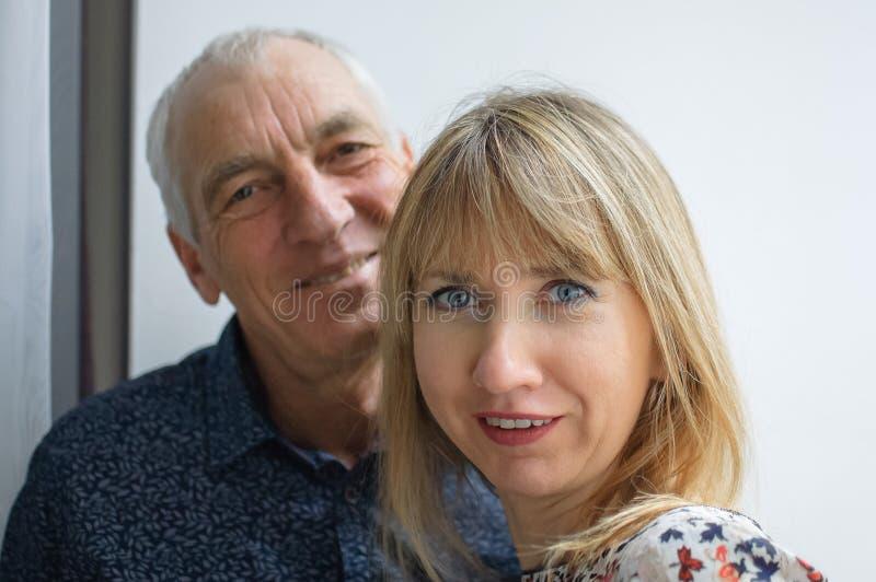 拥抱他的年轻金发的妻子的年长人可爱的浪漫画象穿温暖的礼服 加上年龄 免版税库存图片
