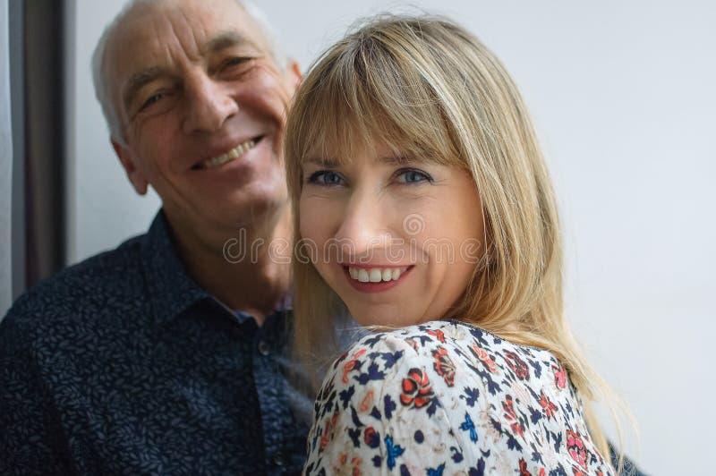 拥抱他的年轻金发的微笑的妻子的年长人可爱的浪漫画象穿温暖的礼服 加上年龄 免版税库存照片
