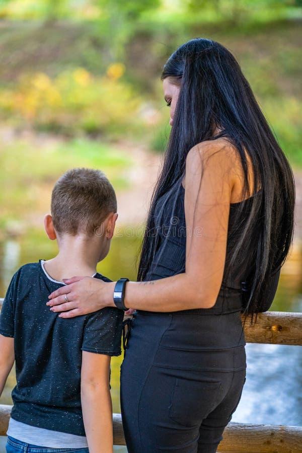 拥抱他的桥梁的孩子妈妈在公园 库存图片