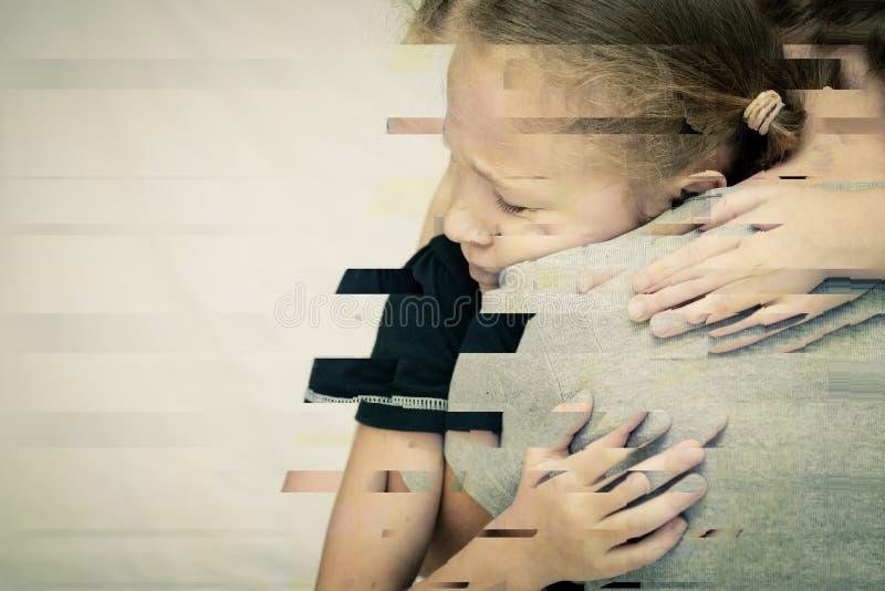 拥抱他的母亲的一个哀伤的女儿的画象 免版税库存照片