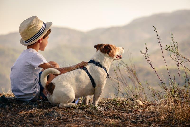 拥抱他的爱犬的孩子看在山景 库存照片