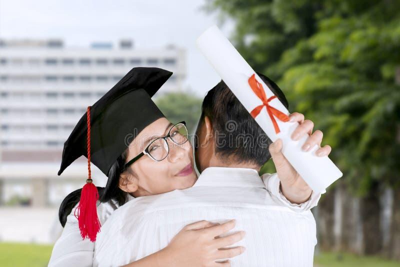拥抱他的男朋友的妇女在毕业生期间 免版税库存照片