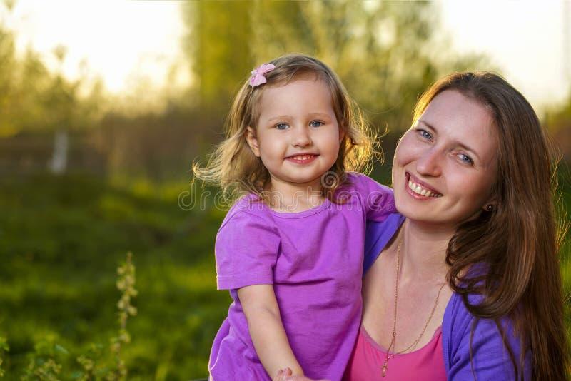 拥抱可爱的白肤金发的女孩和她的母亲画象看照相机和微笑户外 库存图片