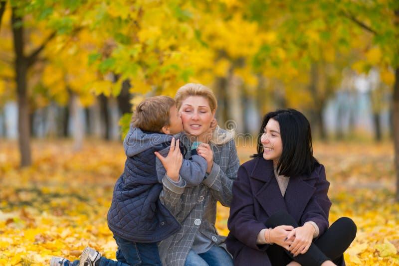 拥抱和亲吻他的母亲的年轻男孩 免版税库存图片