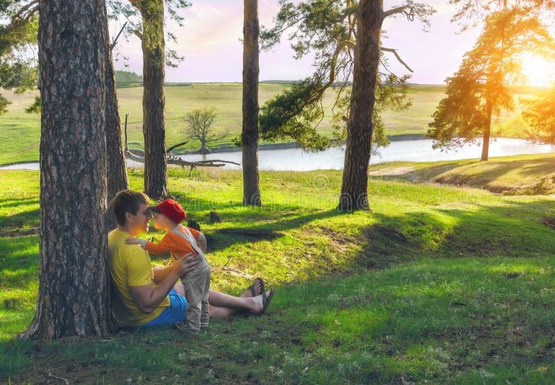 拥抱和亲吻他的父亲的儿子 家庭假日在湖的岸的杉木森林里 库存图片