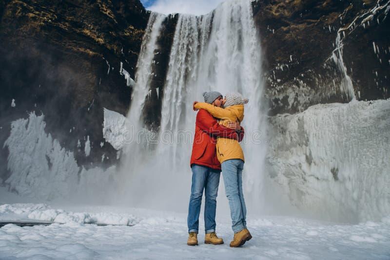 拥抱和亲吻在庄严skogafoss瀑布附近的美好的年轻夫妇在冰岛 免版税库存图片