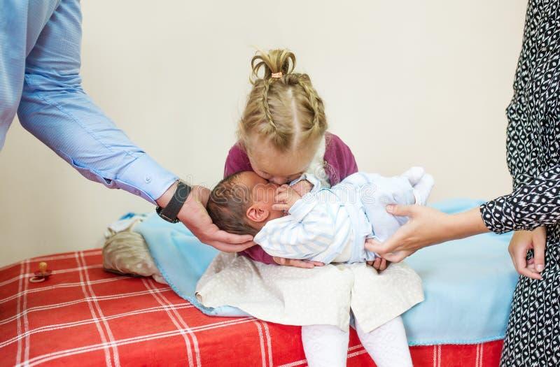 拥抱和亲吻她的男婴兄弟的妹 免版税库存图片