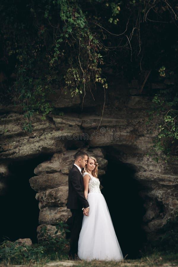 拥抱和亲吻在背景华美的植物和洞的豪华婚礼夫妇在古老城堡附近 免版税库存图片