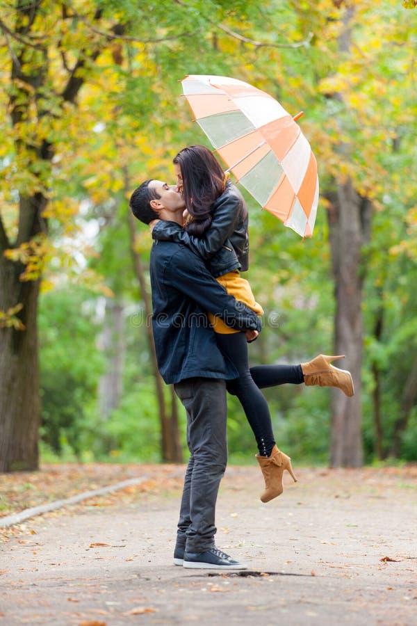 拥抱和亲吻在w的伞下的逗人喜爱的夫妇照片  免版税库存照片