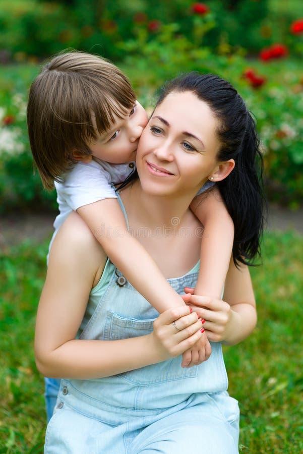 拥抱和亲吻他愉快的母亲的爱恋的儿子  免版税库存图片