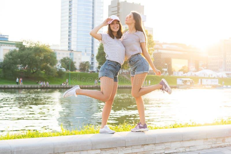 拥抱和嘲笑日落的两个少妇在城市 最好的朋友 免版税库存图片