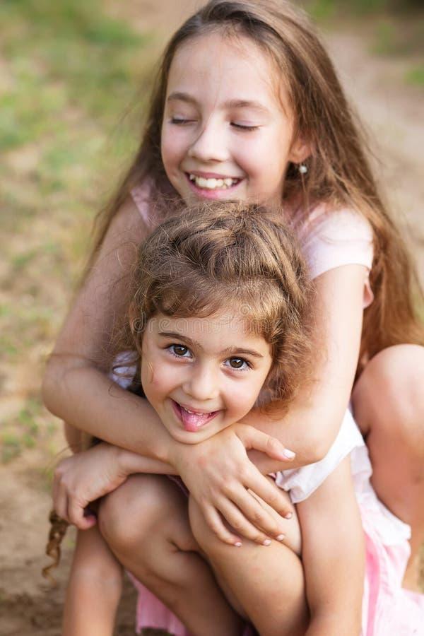 拥抱和嘲笑海边的两个美丽的小女孩 免版税库存图片