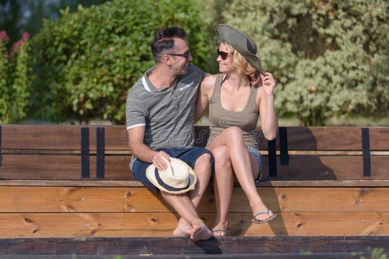 拥抱和坐在湖附近的浪漫夫妇室外 免版税库存图片