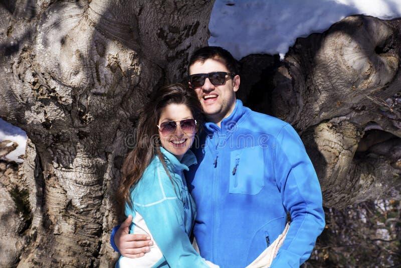 拥抱和微笑在冬天山的美好的微笑的夫妇 免版税库存图片