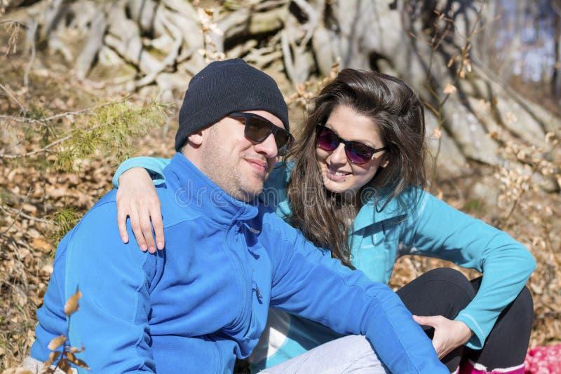 拥抱和微笑在冬天山的美好的微笑的夫妇 库存图片