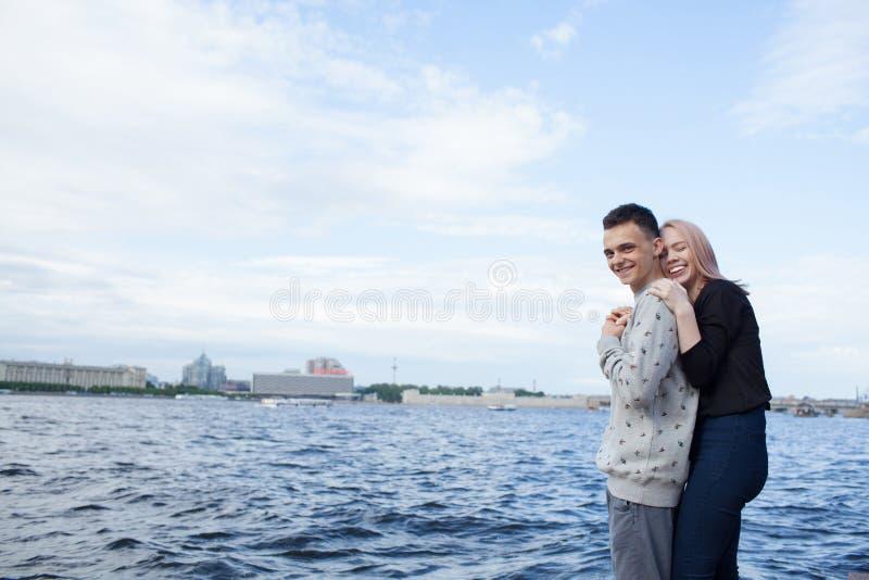 拥抱和微笑在都市风景的背景的年轻夫妇 河堤防在圣彼得堡 免版税库存照片