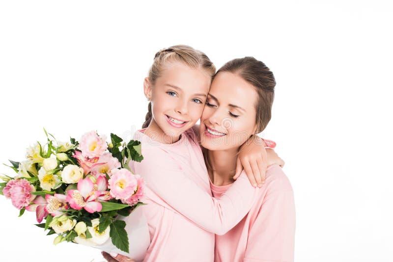 拥抱和拿着花的花束母亲和女儿为母亲节, 库存照片