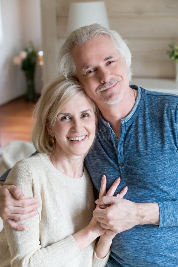 拥抱和握手的愉快的资深夫妇画象  免版税库存照片