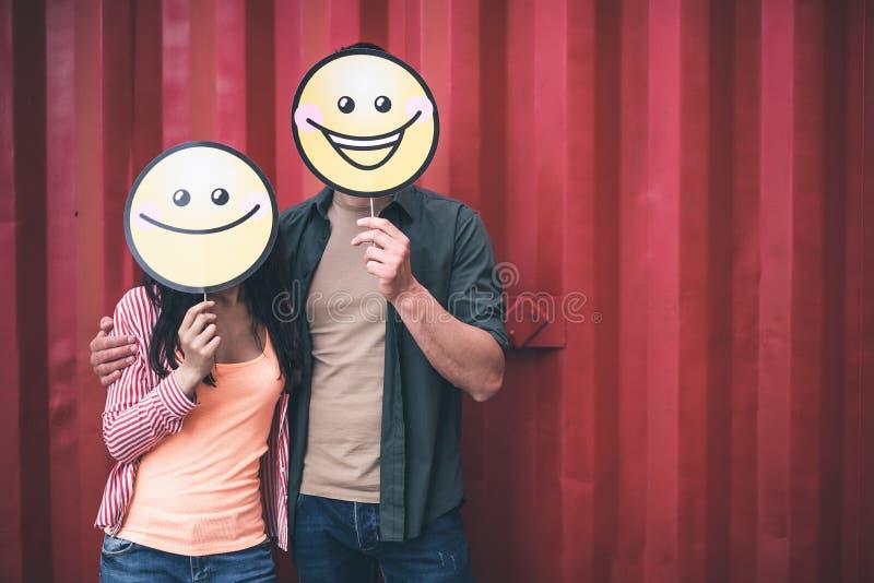 拥抱和摆在与滑稽的图象的可爱的夫妇 免版税库存照片