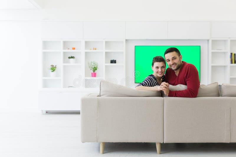 拥抱和放松在沙发的夫妇 免版税库存图片