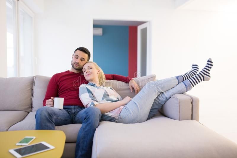 拥抱和放松在沙发的夫妇 库存照片