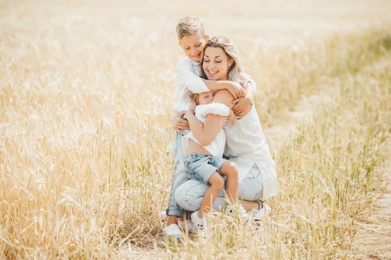 拥抱和爱她的麦田的妈妈小孩 愉快的一起花费时间的母亲和她的孩子户外 库存照片