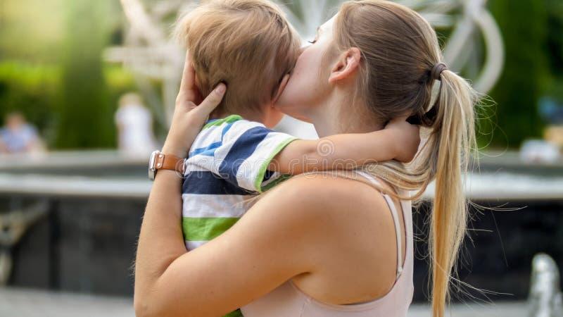 拥抱和爱抚她的年轻母亲特写镜头画象哭泣的小孩男孩在公园 库存图片